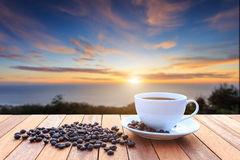 copo-de-café-branco-e-feijões-de-café-na-tabela-de-madeira-e-na-vista-dos-sóis-63184492